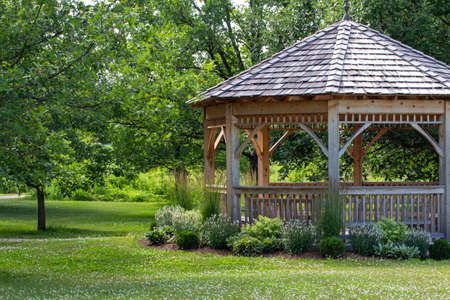 Artfully landscaped wooden gazebo in a sunny botanical garden with trees and grass lawn
