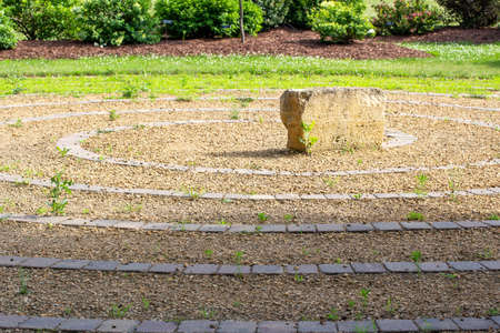 Landscape view of a rustic stone labyrinth walking maze in a public botanical garden park on a sunny day