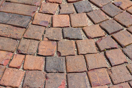 Close up view of a red and brown clay brick walkway with a curved pattern