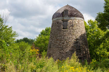 Landscape view of a 19th Century round stone constructed grain windmill preserved in a North American prairie woodland setting
