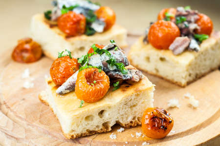Delicious focaccia with sardines and cherry tomatoes on wood photo