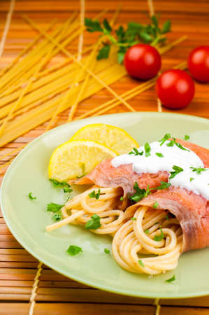 Delicious pasta with somon and tomatoes on green plate photo