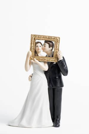 白で隔離されるカップルのウエディング ケーキ トッパー