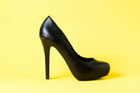 Woman black heel shoe on yellow background  Stock Photo