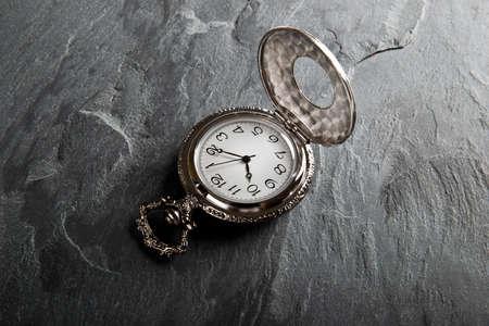 dark slate gray: Pocket gray clock on dark gray slate texture Stock Photo