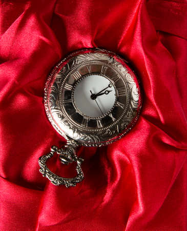 Pocket gray clock on red silk texture photo