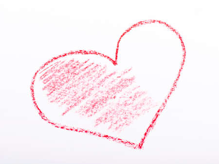Closeup of a red pencil drawing a heart. On white paper. photo
