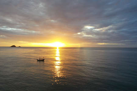 Scenic sunrise with a small fishing boat floating by in Hua Hin Thailand