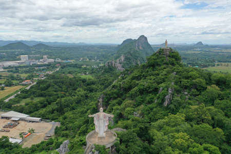 Scenic aerial view of buddhist statue above a mountain view in Ratchaburi Thailand