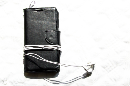 a wallet style smartphone cover with earpods wrapped around it