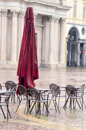 folded parasols and empty chairs in a cafe San Carlo square in Turin Italy during a rain