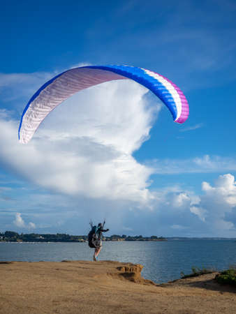 France - August 2020 - On the cliff overlooking the beach, a paraglider soars into the void to take off