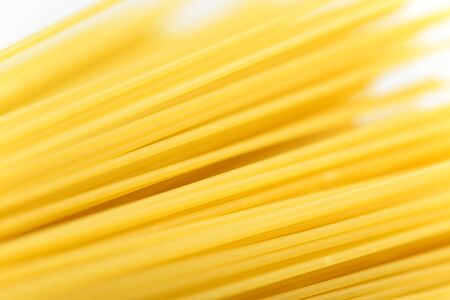 Long yellow spaghetti pasta food ingredient. Uncooked dry macaroni. Thin raw noodle. Cereal wheat product for delicious gourmet cooking. A useful source of carbohydrates. Healthy italian pasta.