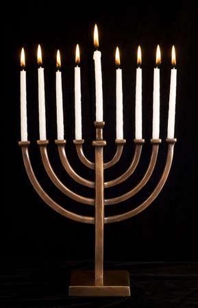 Beautiful lit hanukkah menorah on black velvet.