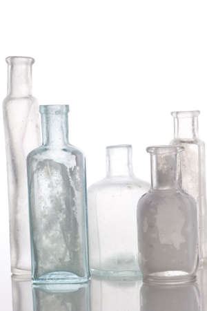 professionally: Antique bottles on white table  Professionally spotted and retouched.