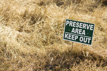 keep out: keep out sign in brown grass preserve area