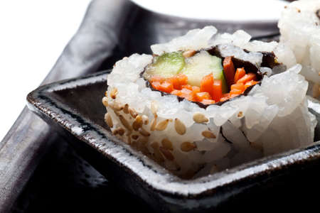 metallic seaweed: Vegetarian sushi California roll with rice and seaweed on Japanese plates