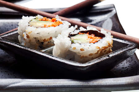 Vegetarian sushi California roll with rice and seaweed on Japanese plates