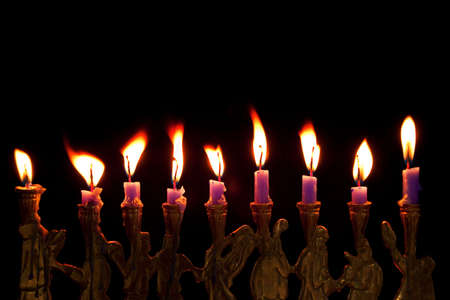 burning hanukkah candles in a menorah on black background photo