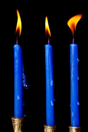burning hanukkah candles in a menorah on black background photo