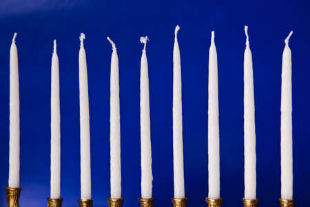 white hanukkah candles in a menorah on blue background photo