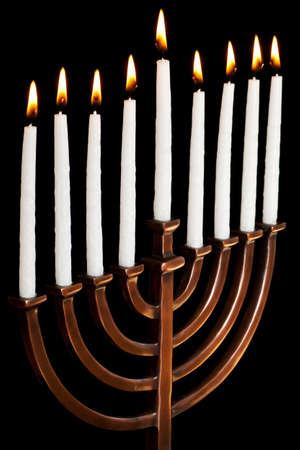 burning hanukkah candles in a menorah on black background