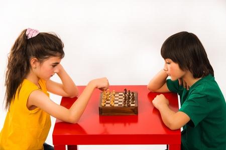 jugando ajedrez: dos ni�os jugando al ajedrez aisladas sobre fondo blanco