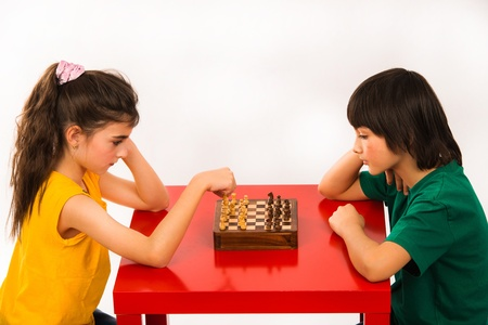 light game: due bambini che giocano a scacchi isolato su sfondo bianco