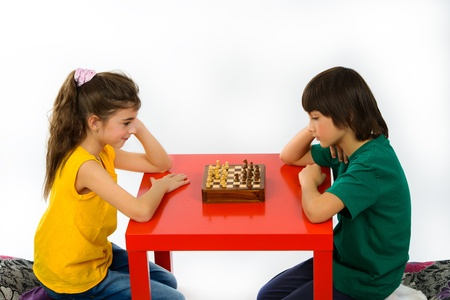 two children playing chess isolated on white background photo