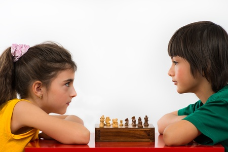two friends: two children playing chess isolated on white background