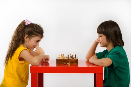two children playing chess isolated on white background