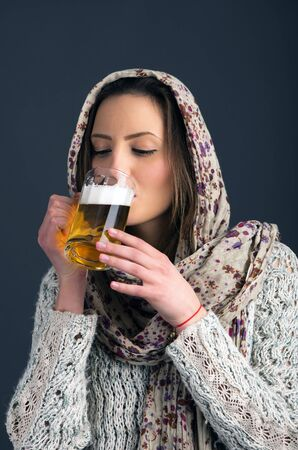 Pretty girl drinking beer from the glass photo