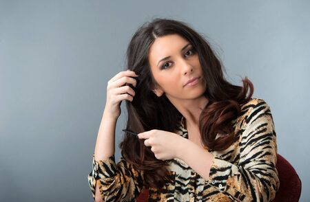 a young brunette woman combing her hair Stock Photo - 18730847