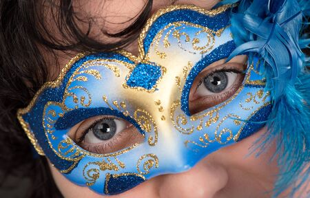 Woman with blue eyes wearing a feathered Venetian mask photo