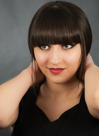 Portrait of a young beautiful woman with bangs in studio Stock Photo - 19050559