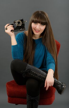 Retro looking young beautiful woman holding a vintage retro camera. Stock Photo - 19050625
