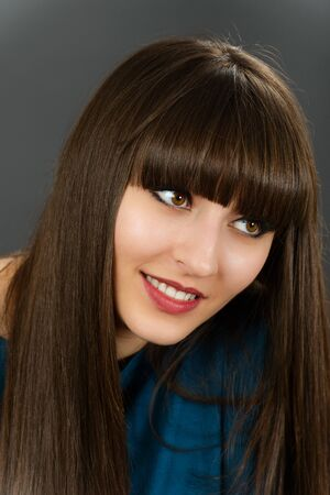 Portrait of a young beautiful woman with bangs in studio Stock Photo - 19050630