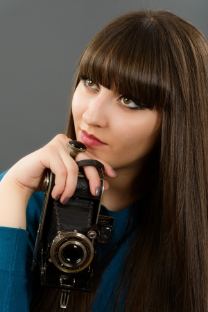 Retro looking young beautiful woman holding a vintage retro camera. photo