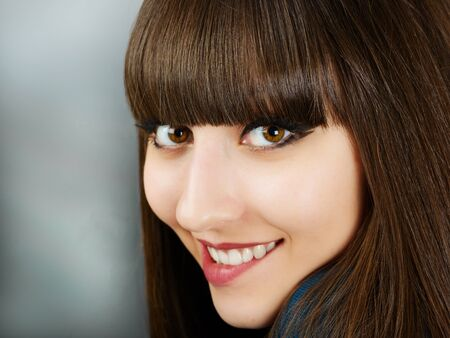 Portrait of a young beautiful woman with bangs in studio photo