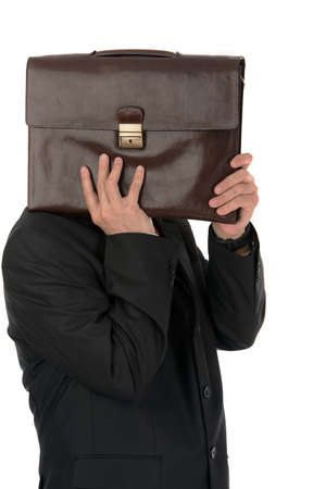 Businessman hiding behind a briefcase isolated on white background photo