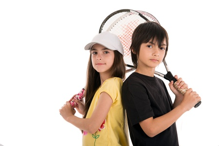 two happy children posing with tennis racquets on white background