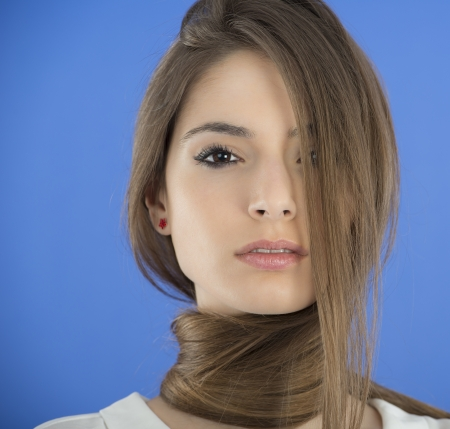 Young Woman with long Hair on blue background Stock Photo
