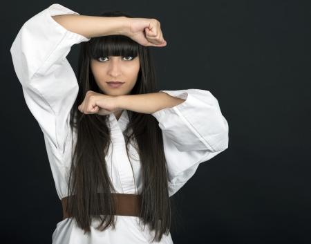 karateka chica asi�tica en el estudio de fondo negro tiro photo