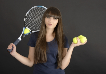 Female tennis player with racket and ball on black background photo