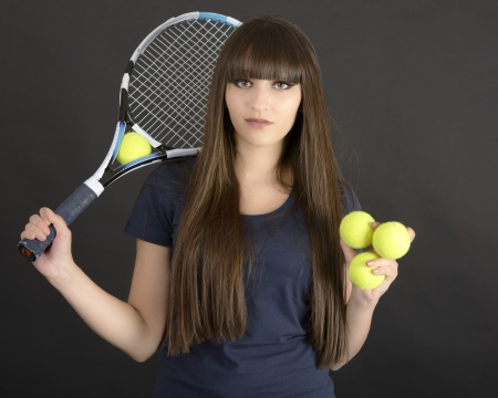 hairband: Female tennis player with racket and ball on black background Stock Photo