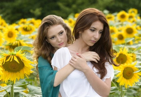 Portrait of a beautiful two happy young women with long hair in sunflowers field photo
