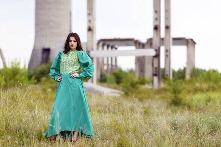 Attractive young lady posing somewhere in industrial ruins Stock Photo