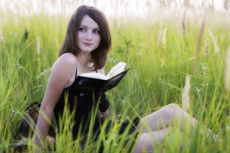 The girl sitting on a grass, reading a book photo