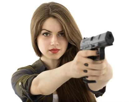 pistolas: Mujer hermosa joven con una pistola sobre fondo blanco Foto de archivo