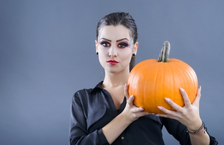beautiful girl with pumpkin in the studio isolated on gray background photo